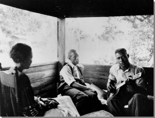 Figure 5: Gabriel Brown playing guitar for Rochelle French and Zora Neale Hurston, Eatonville, Florida, 1935