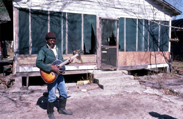 Figure 7: Buck Thompson playing blues guitar outside of his house, Hastings, Florida, 1985