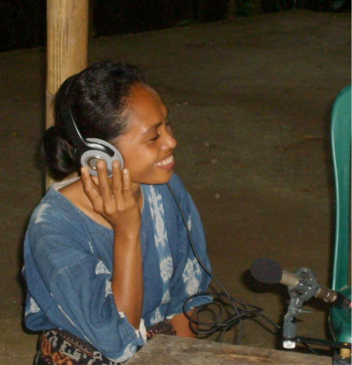 Singer listening to a recording of her own performance in Flores, Indonesia