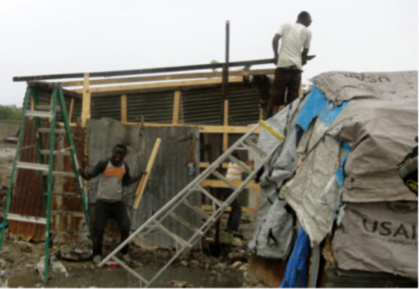 Relief workers repair the roof of a home in Cite Soleil